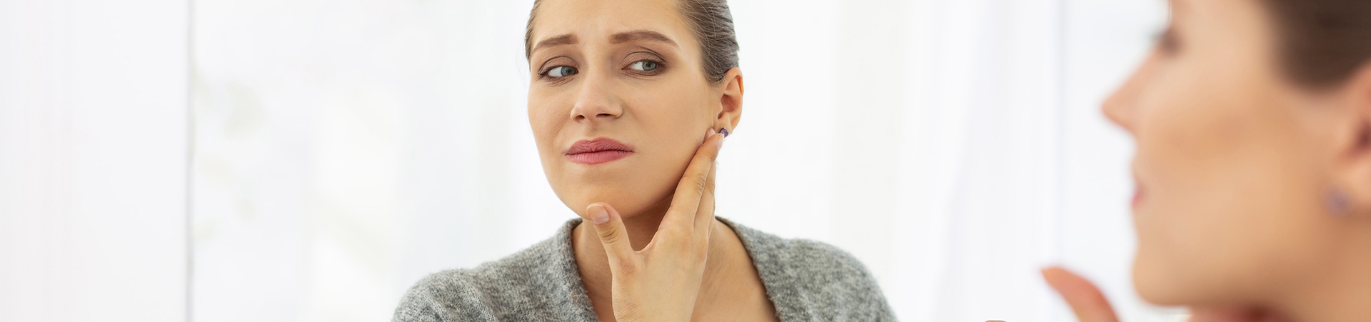 Frowning woman touching her face in front of mirror