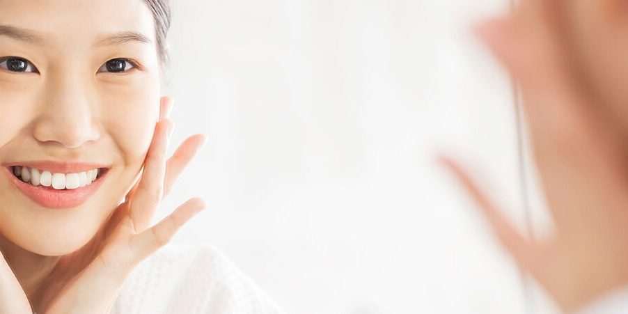 woman looking in mirror while applying moisturizer